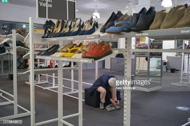 Customer tries on a pair of shoes at a closing down sale at Clarks in Elephant & Castle Shopping Centre in Elephant & Castle on September 23, 2020 in...