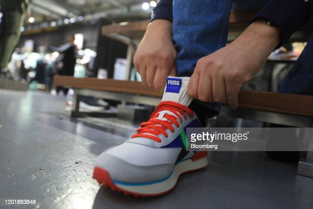 Customer tries on a Puma trainer at the Puma SE concept store in Herzogenaurach, Germany, on Wednesday, Feb. 19, 2020. Puma soared to a record after...