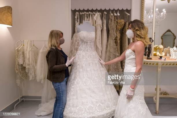 A customer tries on a wedding dress in the atelier of designer Mariella Gennarino of Catania open again to the public after the lockdown on May 6...