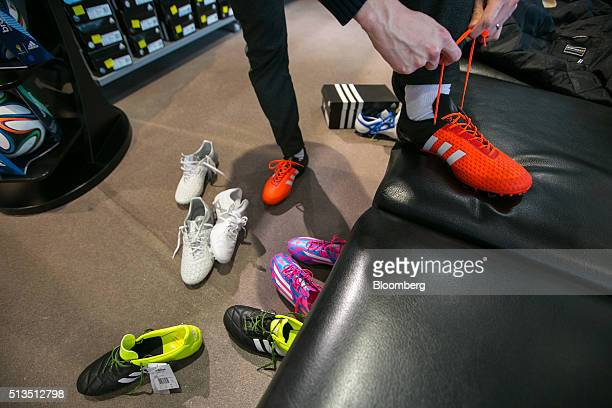 A customer tries on pairs of soccer boots inside the Adidas AG store at the company's headquarters in Herzogenaurach Germany on Thursday March 3 2016...
