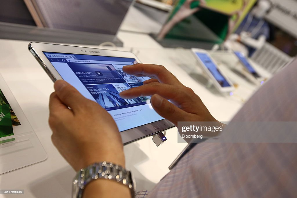 A customer tries out a Samsung Electronics Co. Galaxy Note 10.1 tablet computer at the company's d'light store in Seoul, South Korea, on Monday, July 7, 2014. Samsung Electronics is scheduled to report operating profit and sales figures on July 8. Photographer: SeongJoon Cho/Bloomberg via Getty Images