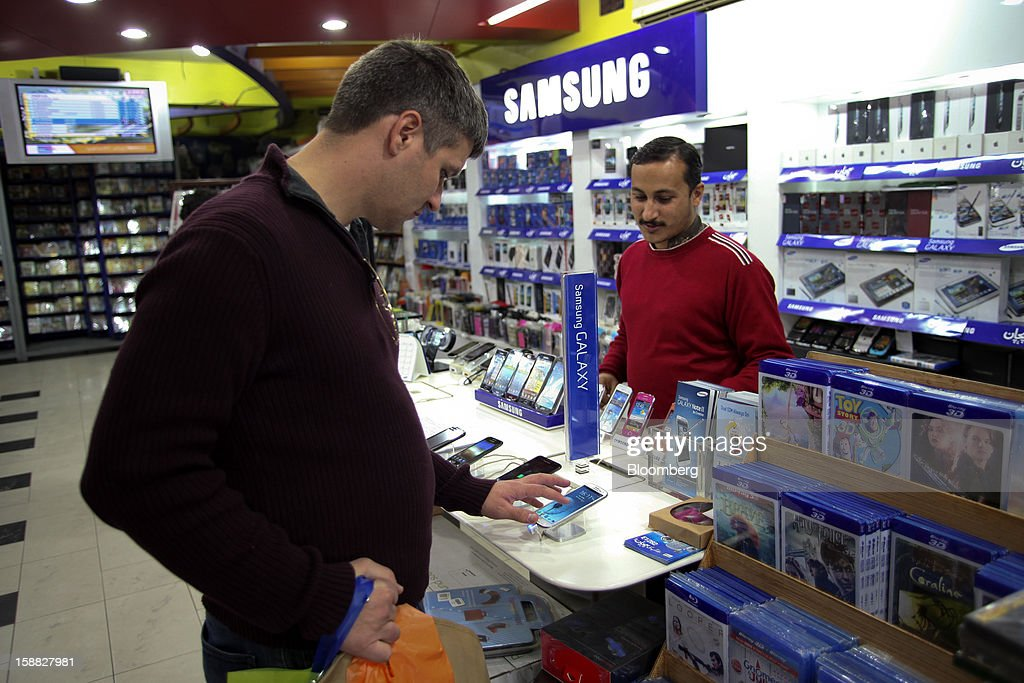 A customer tries out a Samsung Electronics Co. smartphone in Islamabad, Pakistan, on Sunday, Dec. 30, 2012. Pakistan's economy will probably expand 3.5 percent in the 12 months through June, the International Monetary Fund forecast Nov. 29, less than the 4.3 percent predicted by the government. Photographer: Asad Zaidi/Bloomberg via Getty Images