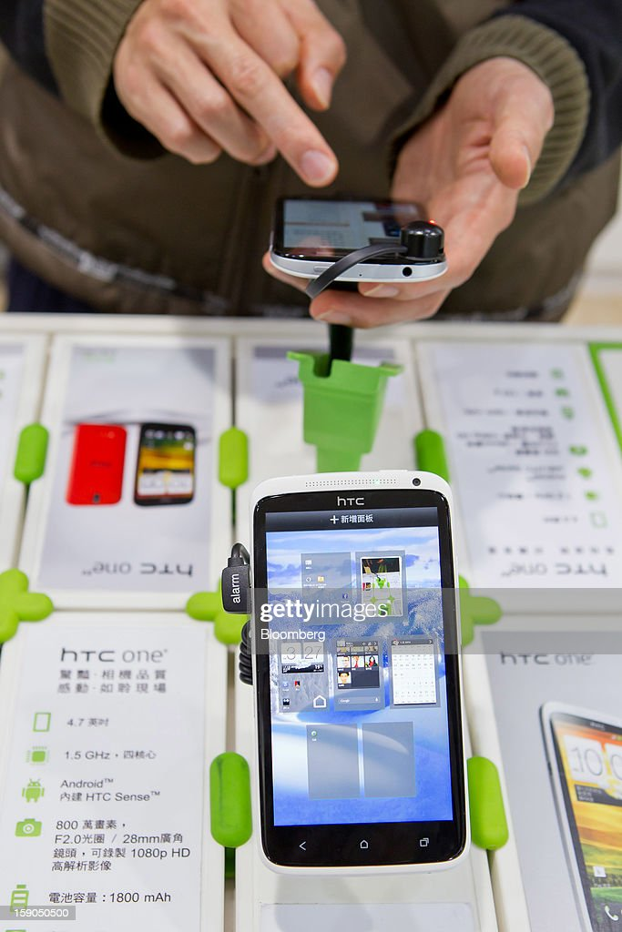 A customer tries out an HTC Corp. One X smartphone at one of the company's stores in Taipei, Taiwan, on Sunday, Jan. 6, 2013. HTC is scheduled to release fourth-quarter earnings on Jan. 7. Photographer: Maurice Tsai/Bloomberg via Getty Images
