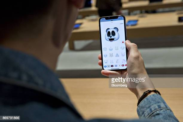 A customer tries out the new Animoji feature of an Apple Inc iPhone X smartphone during the sales launch at a store in Chicago Illinois US on Friday...