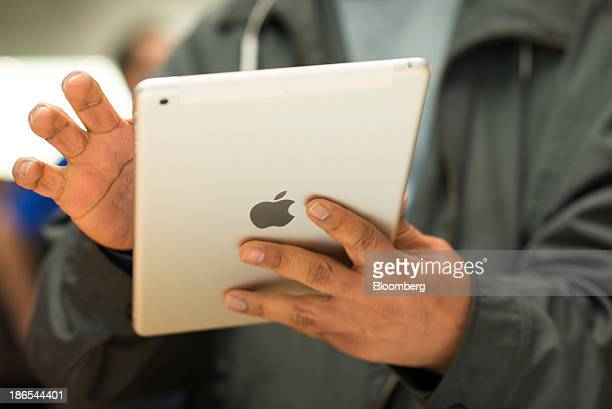 A customer tries out the new Apple Inc iPad Air at the 5th Avenue Apple store in New York US on Friday Nov 1 2013 Apple Inc's forecast for the...