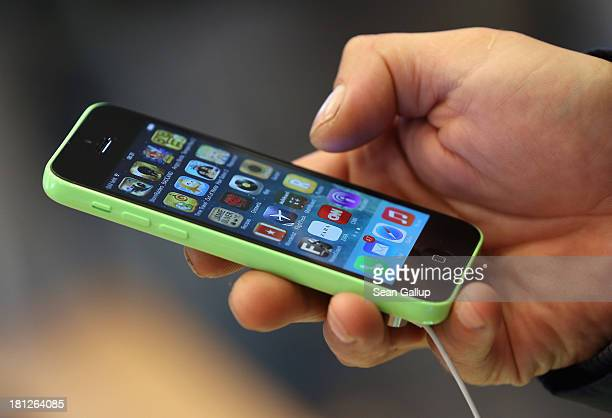 A customer tries out the new Apple iPhone 5C smartphone at the Berlin Apple Store on the first day of sales on September 20 2013 in Berlin Germany...