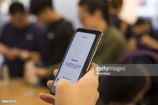 A customer tries the 'Face ID' facialrecognition function on an Apple Inc iPhone X at an Apple store during its launch in Hong Kong China on Friday...