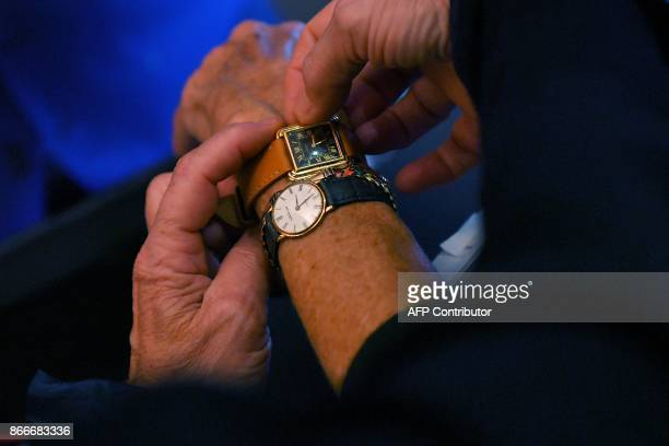 A customer tries watches at a watchmaker shop on October 26 2017 in Nantes western France two days before the end of Daylight Saving Time / AFP PHOTO...
