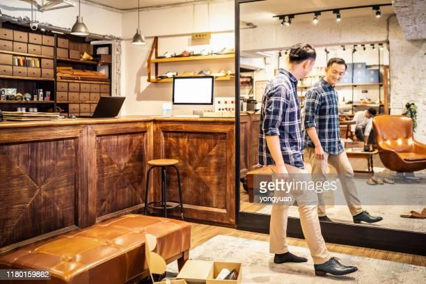 klant probeert een nieuwe leren schoen - the past stockfoto's en -beelden