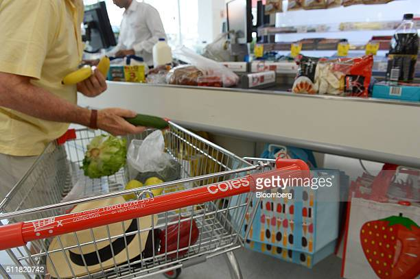 A customer unloads items from his shopping cart at a checkout counter in a Coles supermarket operated by Wesfarmers Ltd in Melbourne Australia on...
