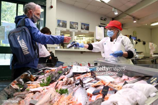 Customer uses a bank card to contactlessly pay for his purchase at a fresh fish stall inside Cardiff Market in Cardiff, south Wales on October 20...