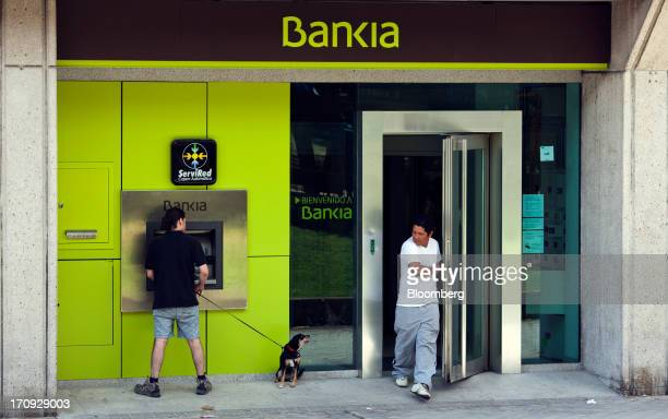 A customer uses a Bankia SA automated teller machine as another exits the bank in Madrid Spain on Wednesday June 19 2013 Bailing out Bankia SA...