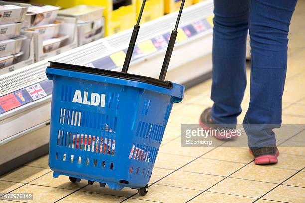 A customer uses a blue plastic shopping basket branded with the Aldi name as they shop inside an Aldi supermarket store in London UK on Monday June...