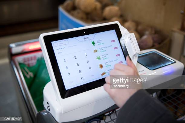 A customer uses a Caper Inc smart shopping cart at a Foodcellar Co grocery store in the Long Island City neighborhood in the Queens borough of New...