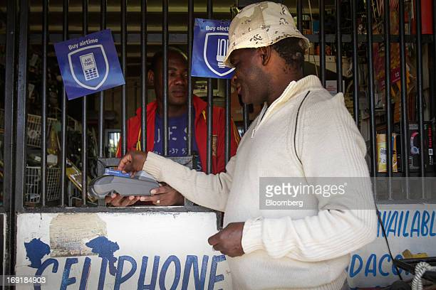 A customer uses a card reader machine at an MPesa mobile phone money transfer point operated by Standard Bank Group Ltd at a store in Tembisa near...