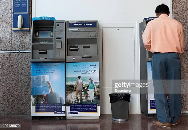 A customer uses a cheque deposit machine inside an Emirates NBD PJSC bank in Dubai United Arab Emirates on Sunday Oct 16 2011 Emirates NBD PJSC the...