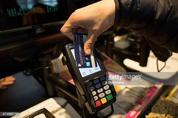 A customer uses a credit card to make a contactless payment on a Verifone Systems Inc payment device in London UK on Friday May 22 2015 Credit and...