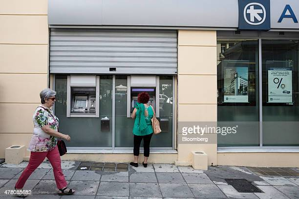 A customer uses a half shuttered automated teller machine outside an Alpha Bank AE bank branch in Thessaloniki Greece on Monday June 22 2015 Dutch...