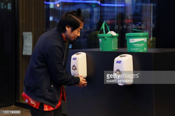 A customer uses a hand sanitiser before attending a screening of the European Premiere of Disney's MULAN at the Odeon Luxe Leicester Square cinema in...