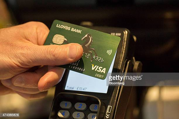 A customer uses a Lloyds Bank Visa Inc debit card to make a contactless payment on a Verifone Systems Inc payment device in London UK on Friday May...