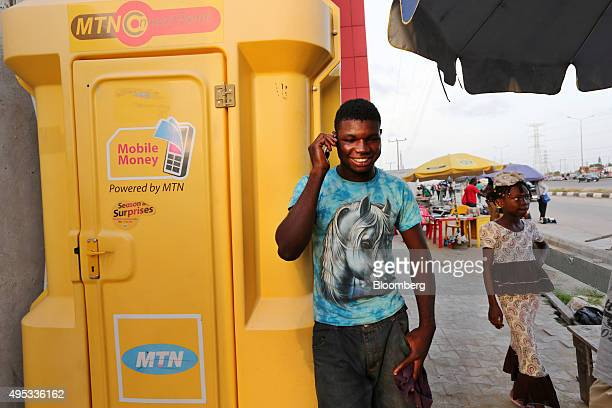 """Customer uses a mobile phone beside an MTN Group Ltd. """"Connect Point"""" in Lagos, Nigeria, on Saturday, Oct. 31, 2015. MTN, Africa's largest wireless..."""