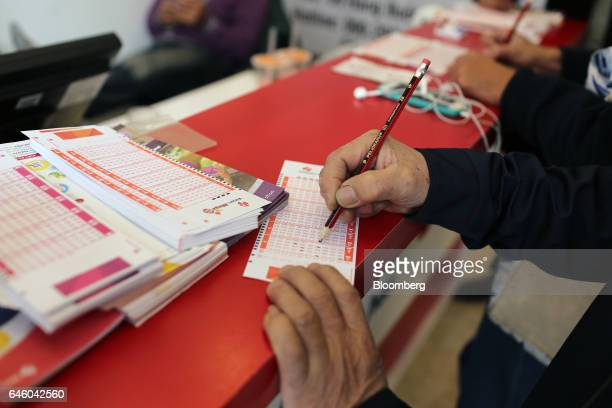 A customer uses a pencil to fill out a lottery form at a store of Vietnam Lottery Co a government partnership with Berjaya Corp in Hanoi Vietnam on...