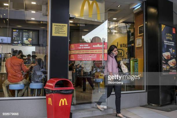 A customer uses a smartphone while exiting a McDonald's Corp restaurant operated by Hardcastle Restaurants Pvt in Mumbai India on Tuesday March 20...