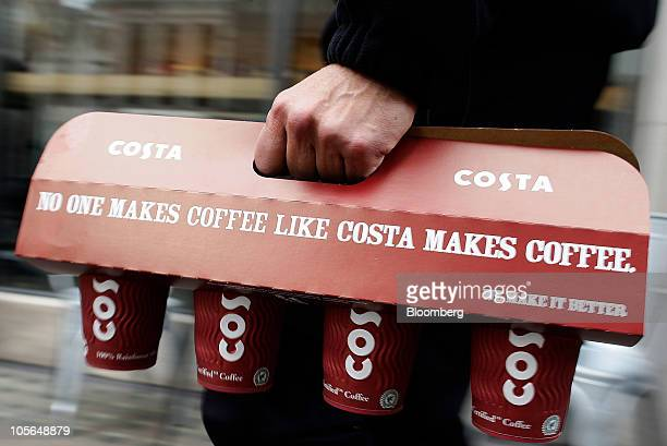 A customer uses a specialized coffee holder to carry take out drinks form a Costa Coffee shop in London UK on Monday Oct 18 2010 Whitbread Plc which...