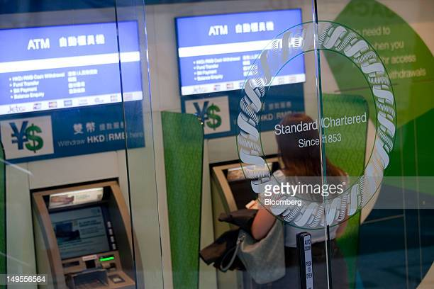 A customer uses a Standard Chartered Plc automated teller machine at one of the bank's branches in Hong Kong China on Monday July 30 2012 Standard...