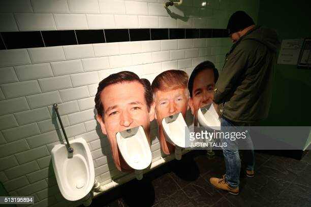 A customer uses a urinal with a cardboard cut out of Republican nomination candidate for the 2016 US Presidential election Marco Rubio seen next to...