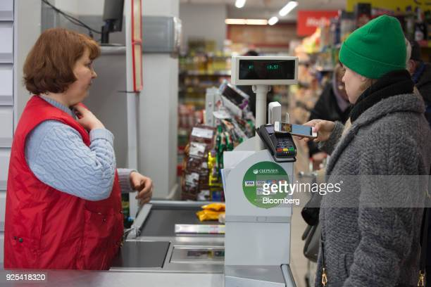A customer uses an Apple Inc iPhone Electronic Apple Pay mobile payment inside a Magnit PJSC supermarket store in Moscow Russia on Wednesday Feb 28...