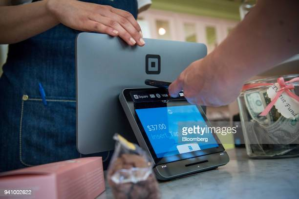 A customer uses an Apple Inc iPhone to make a payment on a Square Inc device in San Francisco California US on Tuesday March 27 2018 The mobile...