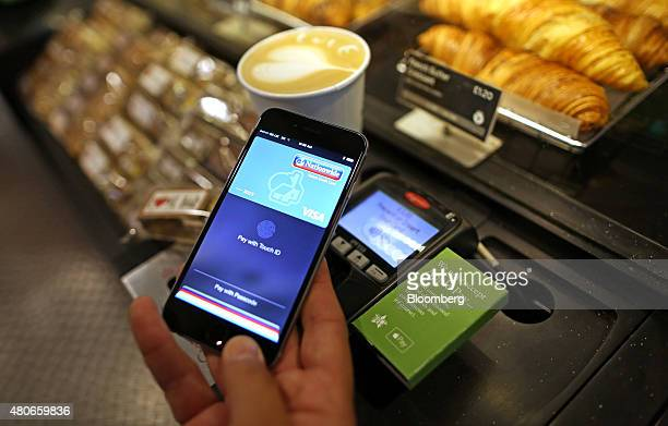 A customer uses an Apple Inc iPhone to pay via the Apple Pay system from their Nationwide account at the checkout till inside a Pret A Manger Ltd...