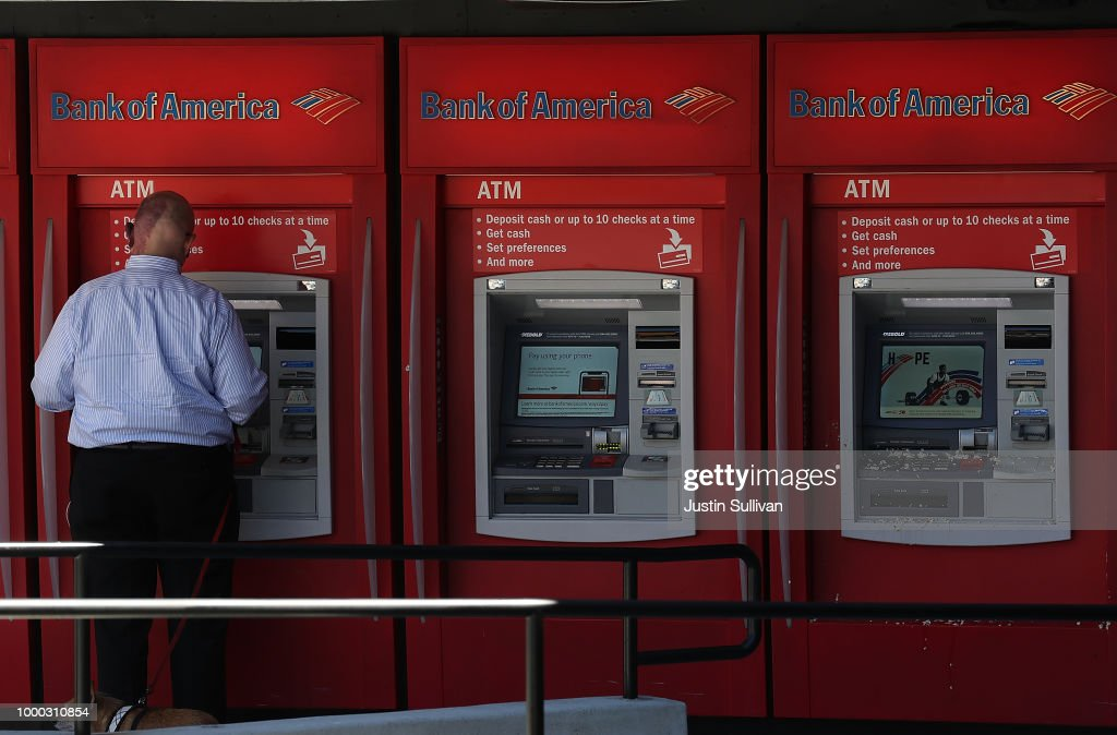 A customer uses an ATM machine at a Bank of America office