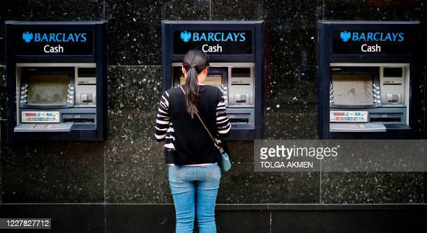 A customer uses an ATM machine outside a branch of a Barclays bank in central London on July 29 2020 British bank Barclays said Wednesday that...