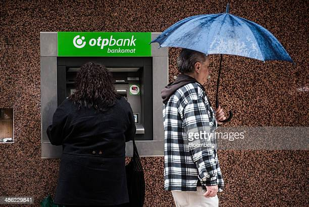 A customer uses an automated teller machine as a pedestrian carries a blue umbrella outside an OTP Bank Nyrt bank branch in Budapest Hungary on...