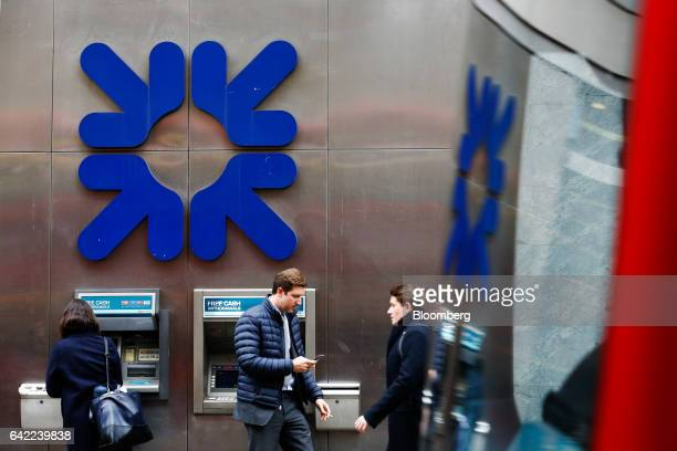 A customer uses an automated teller machine as commuters pass below a logo hanging on a wall outside a Royal Bank of Scotland Group Plc bank branch...