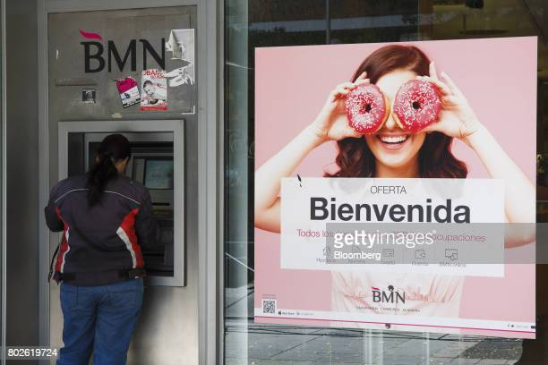 A customer uses an automated teller machine at a Banco Mare Nostrum SA bank branch in Madrid on Wednesday June 28 2017 Bankia SAagreed to...