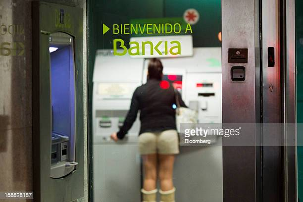 A customer uses an automated teller machine at a Bankia SA bank branch in Madrid Spain on Sunday Dec 30 2012 Spain is seeking to clean up the...
