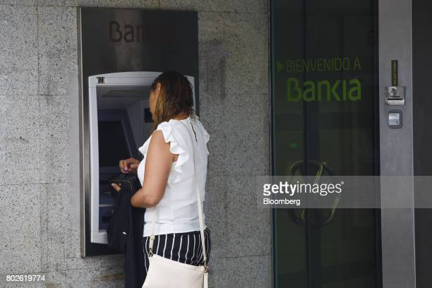 A customer uses an automated teller machine at a Bankia SA bank branch in Madrid on Wednesday June 28 2017 Bankia SAagreed to acquireBanco Mare...