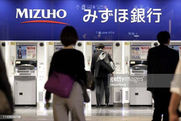 Customer uses an automated teller machine at a branch of Mizuho Bank Ltd., a unit of Mizuho Financial Group Inc. , in Tokyo, Japan, on Friday, May...
