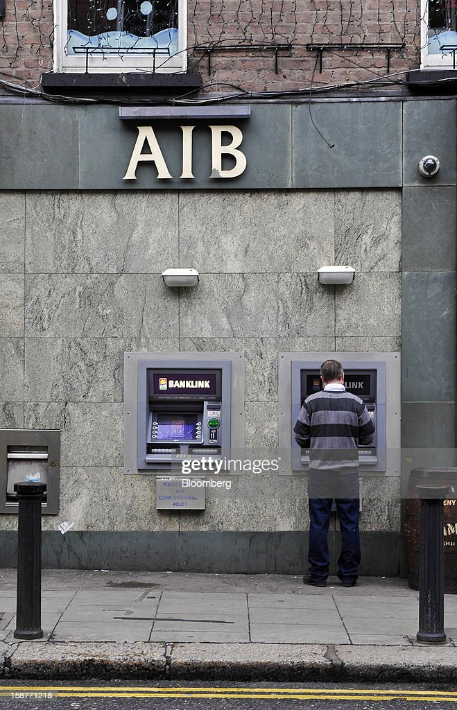 A customer uses an automated teller machine (ATM) at an Allied Irish Bank (AIB) branch in Dublin, Ireland, on Friday, Dec. 28, 2012. Ireland will take over the EU presidency in January as the euro-area wrestles with putting the European Central Bank in charge of lenders within the currency union and other participating nations. Photographer: Aidan Crawley/Bloomberg via Getty Images