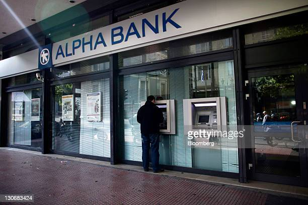 A customer uses an automated teller machine at an Alpha Bank SA branch in Athens Greece on Thursday Oct 27 2011 The new package will reduce debt by...