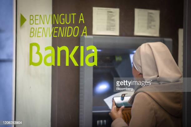 A customer uses an automated teller machine inside a Bankia SA bank branch in Barcelona Spain on Monday March 9 2020 Spanish bank shares soared after...