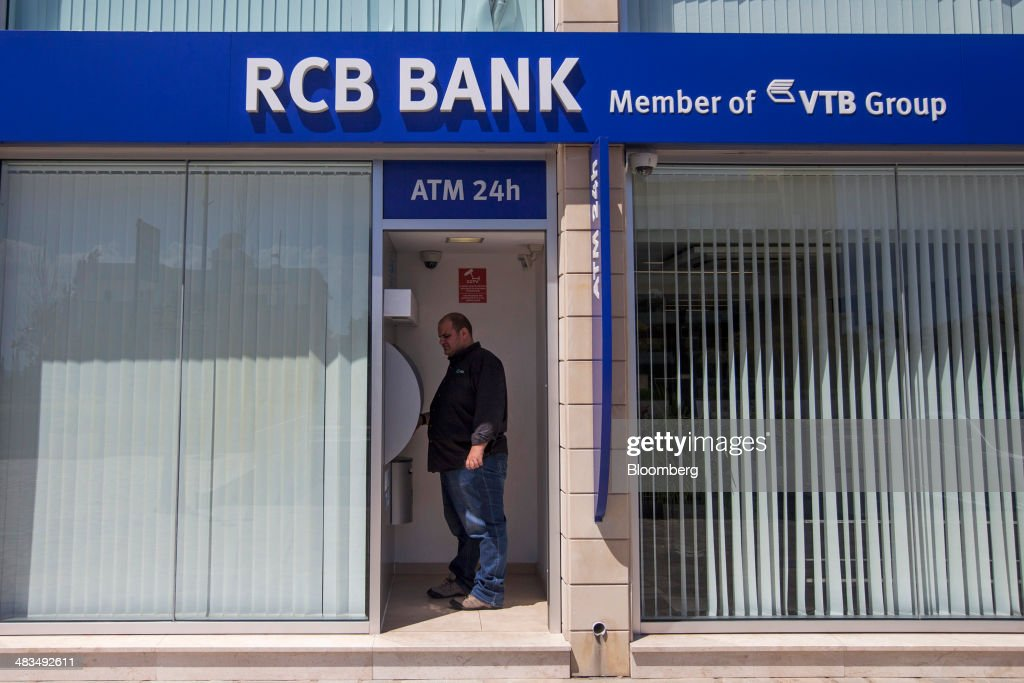 A customer uses an automated teller machine (ATM) inside a Russian Commercial Bank Cyprus Ltd. (RCB) bank branch in Limassol, Cyprus, on Tuesday, April 8, 2014. Cyprus wants to shield financial flows with Russia, where it's the biggest foreign investor, as the U.S. and the European Union ratchet up sanctions in response to President Vladimir Putin's annexing Crimea from Ukraine. Photographer: Andrew Caballero-Reynolds/Bloomberg via Getty Images