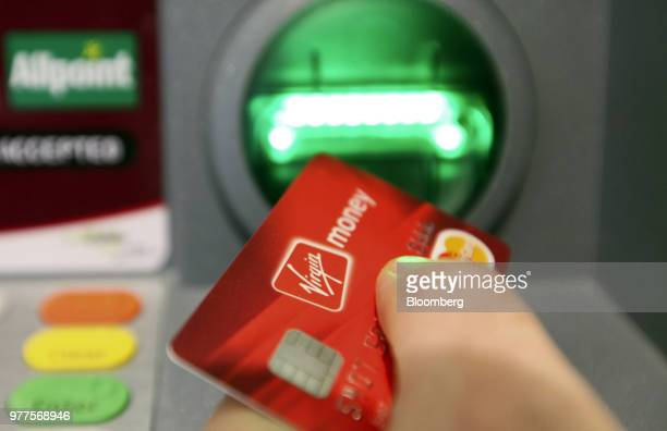 A customer uses an automated teller machine inside the Virgin Money Holdings UK Ltd's 'Money Lounge' in this arranged photograph in Norwich UK on...