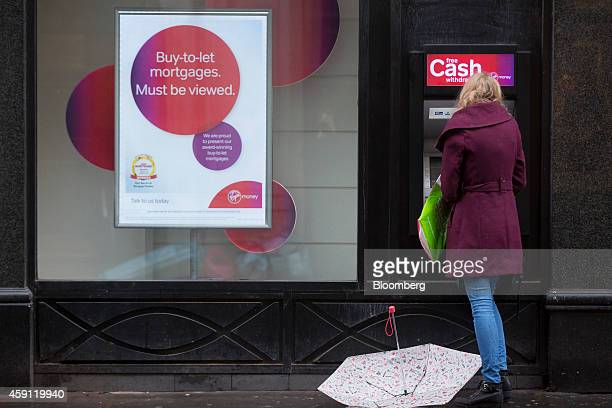 A customer uses an automated teller machine operated by Virgin Money Holdings Plc outside a bank branch in London UK on Monday Nov 17 2014 Virgin...
