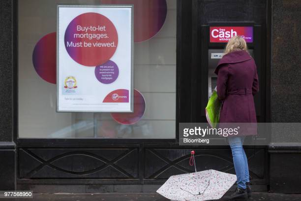 A customer uses an automated teller machine operated by Virgin Money Holdings Plc outside a bank branch in London UK on Monday Nov 17 2014 CYBG Plc...
