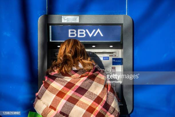 A customer uses an automated teller machine outside a Banco Bilbao Vizcaya Argentaria SA bank branch in Barcelona Spain on Saturday March 7 2020...