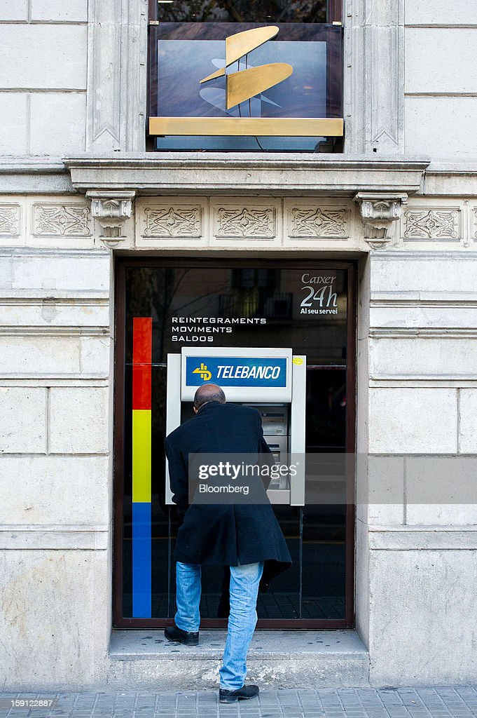 A customer uses an automated teller machine (ATM) outside a Banco Espanol de Credito SA (Banesto) bank branch in Barcelona, Spain, on Tuesday, Jan. 8, 2013. Banco Santander SA, Spain's biggest lender, will offer 263 million euros ($345 million) in stock to buy out minority investors in its Banco Espanol de Credito SA retail unit and close 700 local branches to cut costs. Photographer: David Ramos/Bloomberg via Getty Images